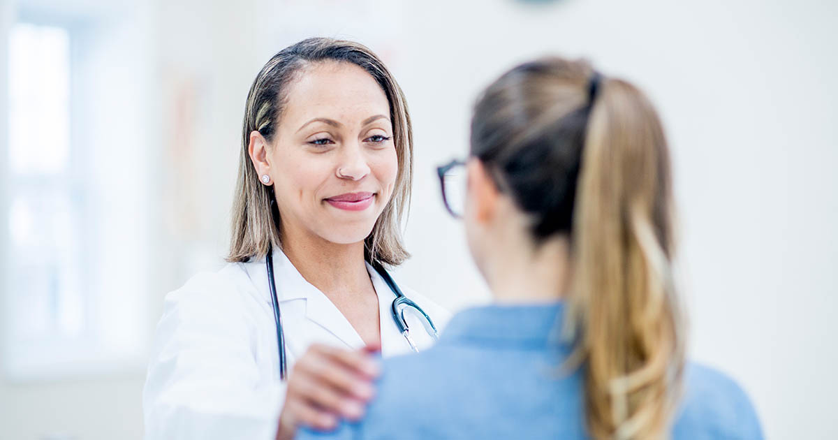 Female doctor talking to young female patient