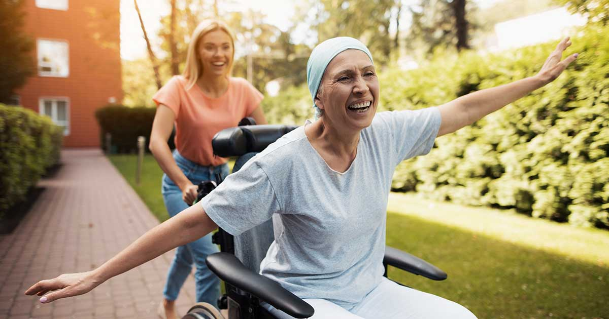 Smiling female cancer patient in a wheelchair being pushed