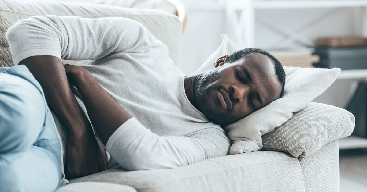 Man lying on couch holding abdomen