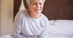 Senior woman experiencing cramps or stomach pain