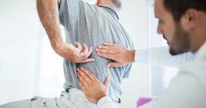 Senior man pointing to back pain as doctor examines