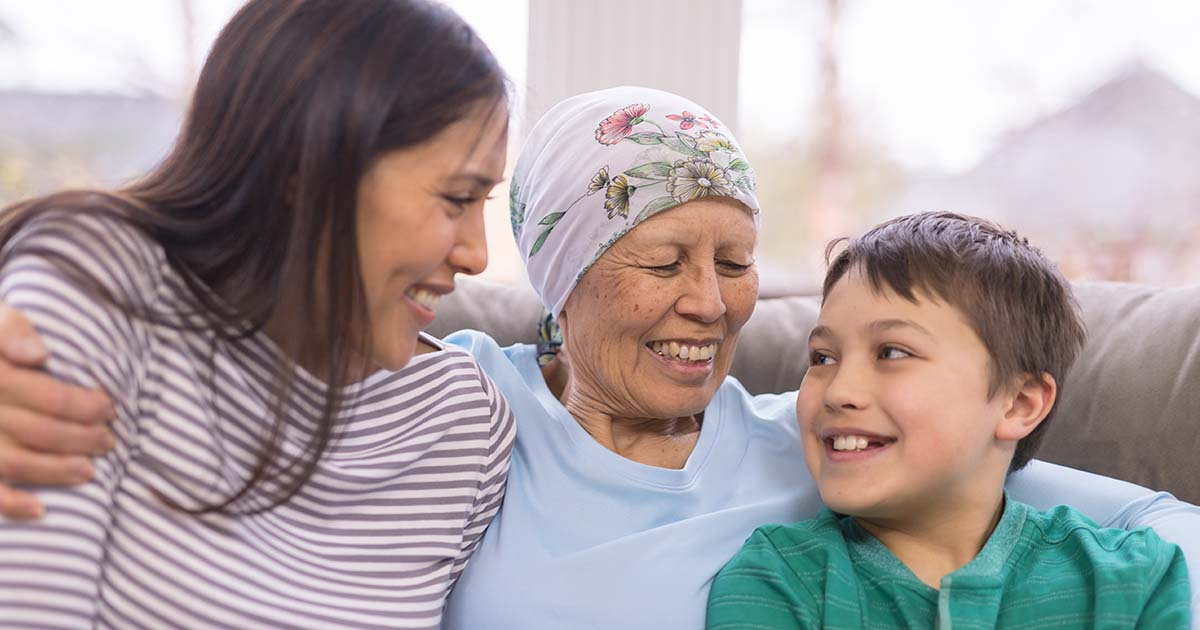 Mature female cancer patient talking to daughter and grandchild