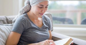 Woman wearing a head scarf reading a book
