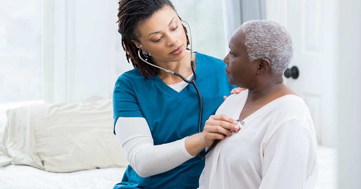 Female nurse checking senior female patient's heart