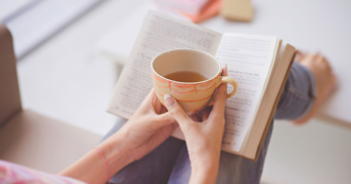 A person is reading while enjoying a cup of tea
