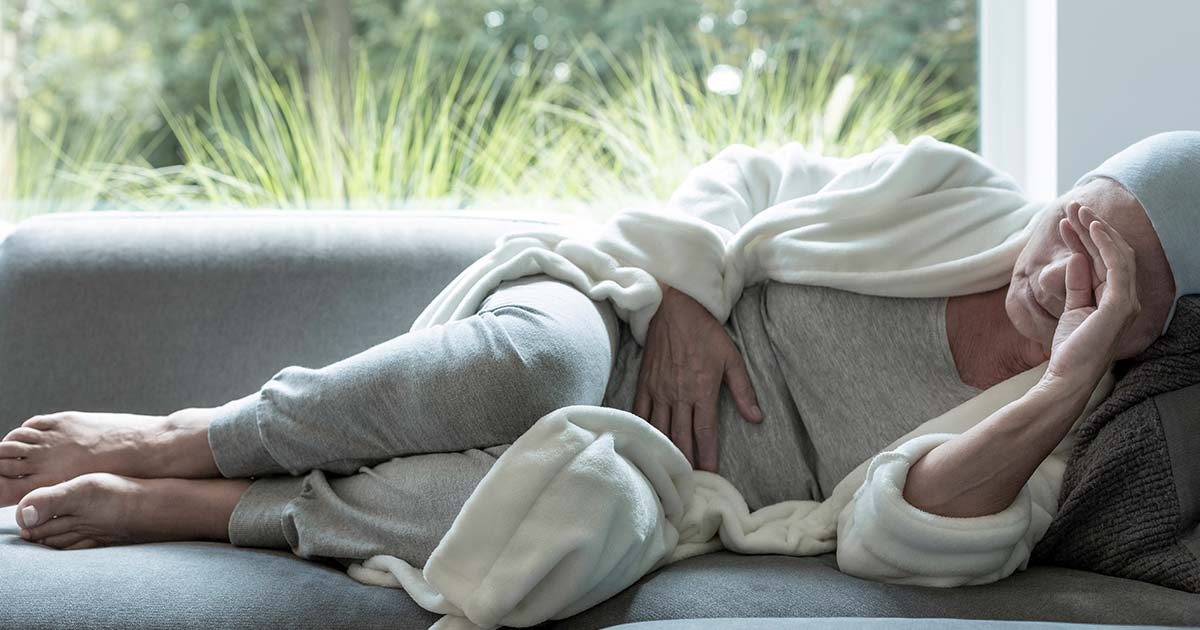 Female cancer patient feeling nauseous is lying on a sofa