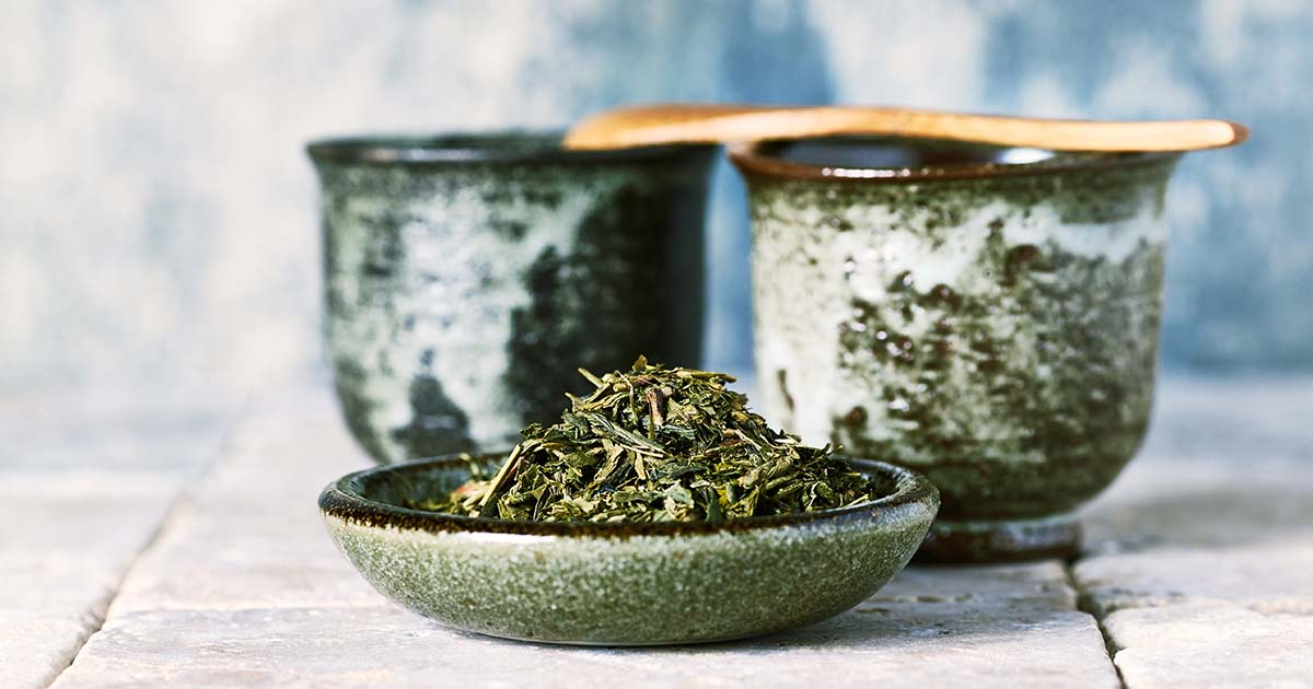 Sencha green tea leaves and Japanese ceramic tea cups