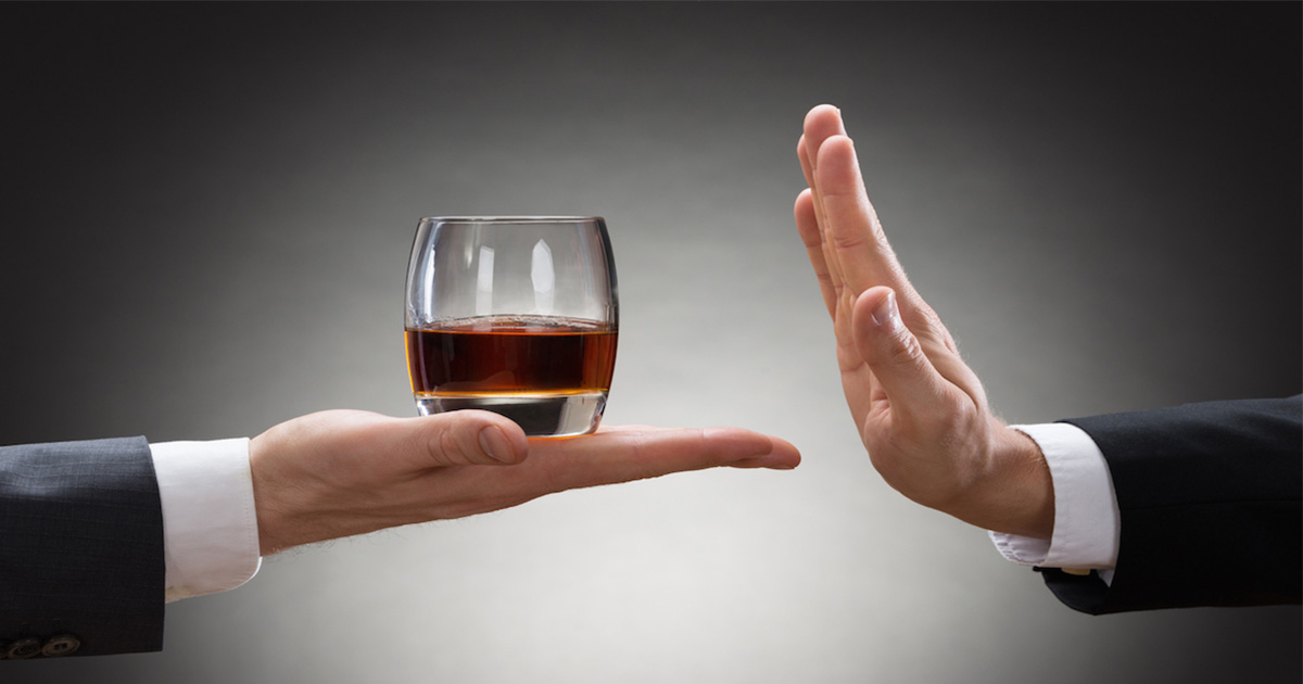 Man holding a glass of alcohol out and another hand saying no