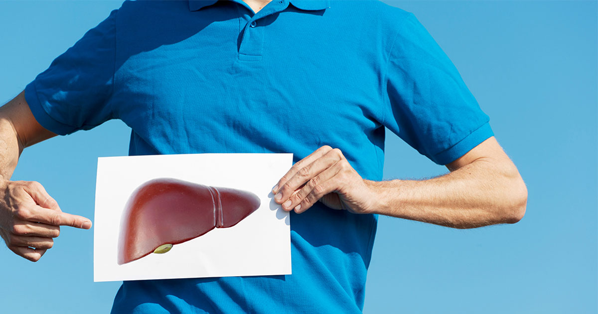Man holding a photo of a liver by his abdomen and pointing to it