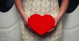 Woman holding a wooden heart near abdomen
