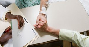 Doctor writing in folder while patient holds hands with family member