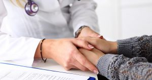 Doctor holding the hands of patient across the table