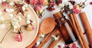 Essential oil vial and flowers with cinnamon sticks on a table