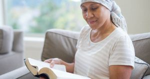 Woman wearing head scarf reading on a couch