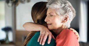 Older woman hugging her daughter
