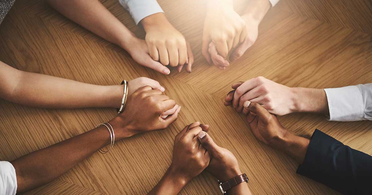 Closeup shot of a group of people sitting together at a table and holding hands