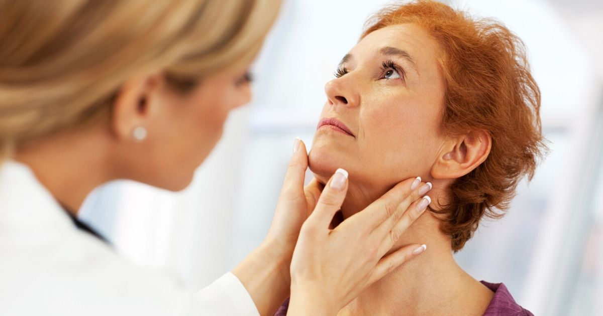 a doctor examining her female patient for head and neck cancer