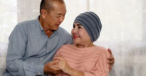 a man supporting his wife after she successfully completed chemotherapy treatment