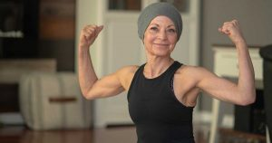 a cancer survivor flexing her muscles and staying positive, which is one of the best tips for cancer survivors