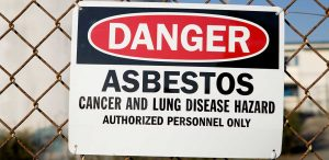 an asbestos warning sign: one of the many cancer causing substances