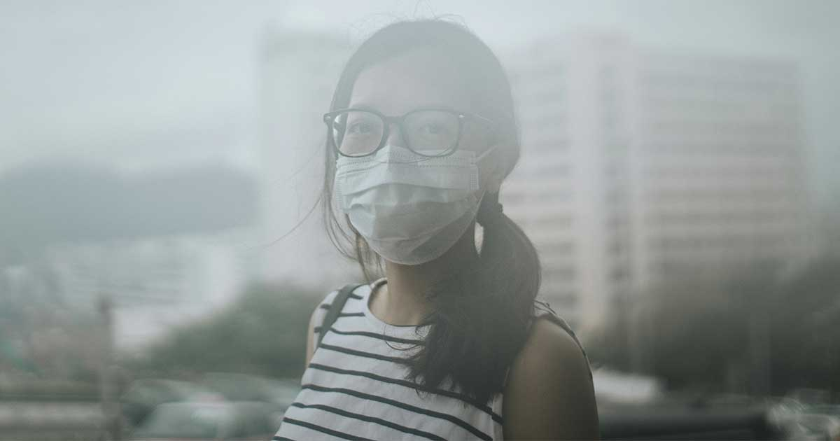 a woman wearing a face mask outside to protect her against air pollution (which is one of the examples of carcinogens)