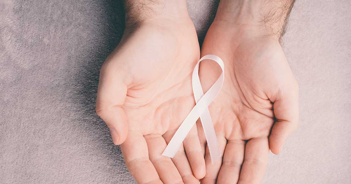 male hands holding a breast cancer awareness ribbon