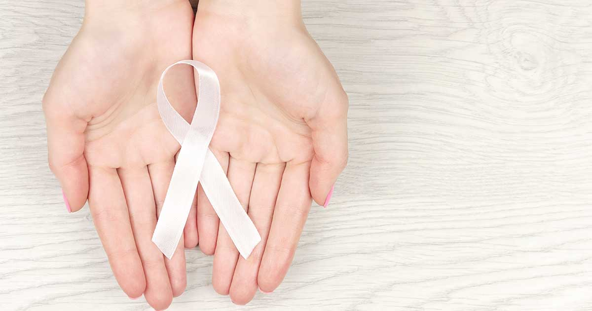 A pair of hands holding a white lung cancer awareness ribbon.