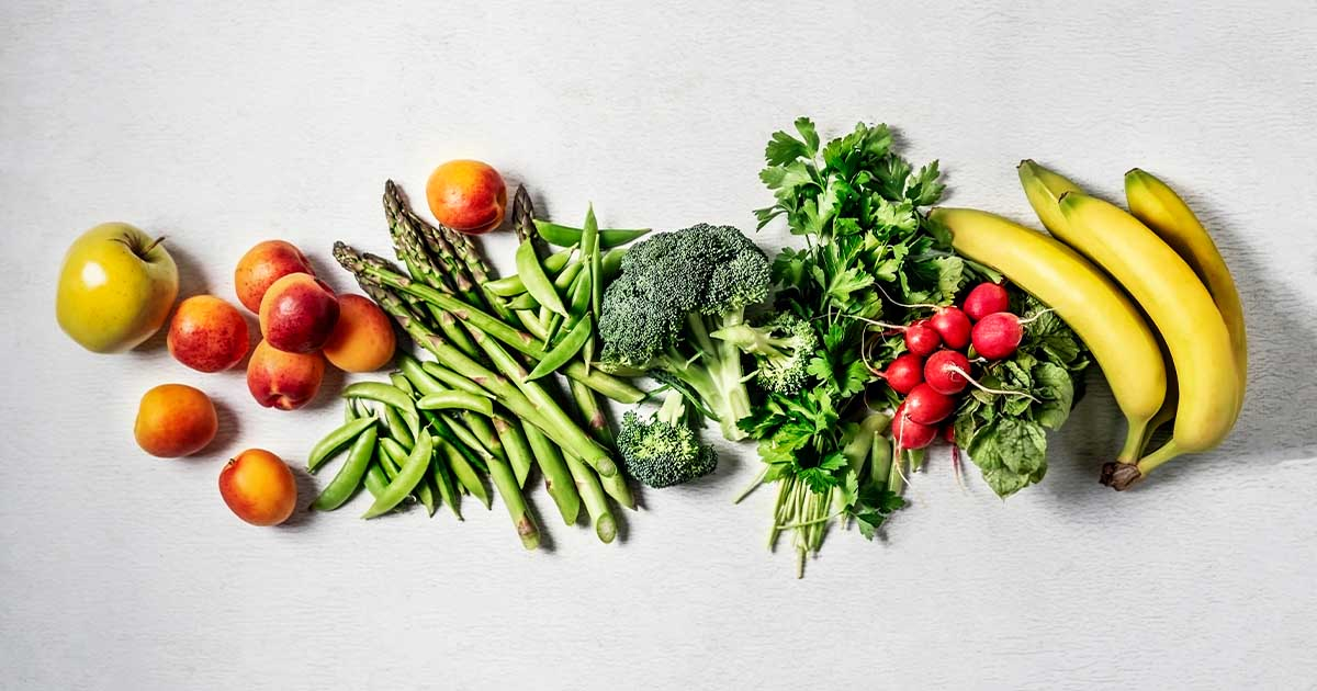 A row of vegetables and fruits against a white background.